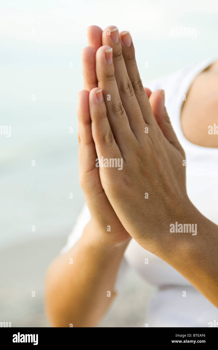 Woman's clasped hands in prayer position - Stock Image