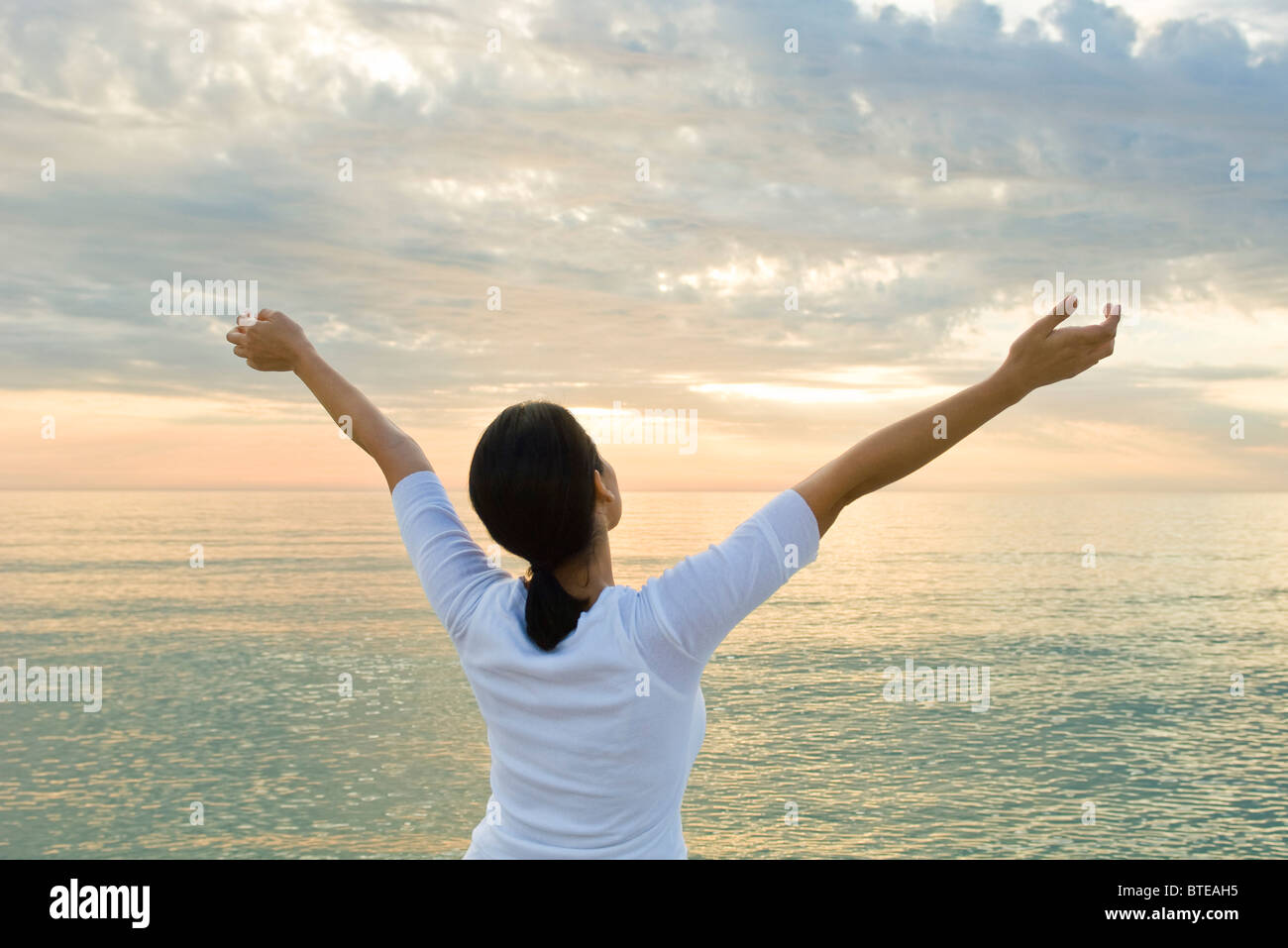 Woman watching sunset at the beach, arms raised in the air - Stock Image