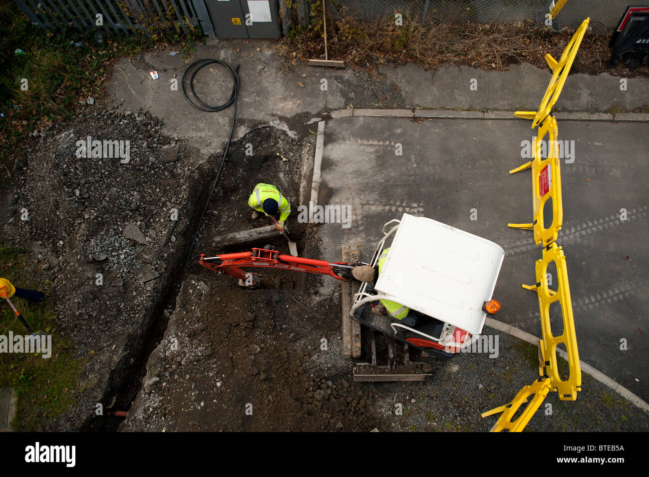 Mini excavator digging a trench , viewed from above,  UK - Stock Image
