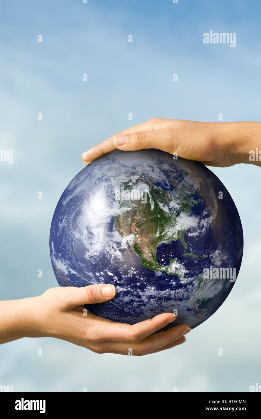 Two people's hands supporting one ball - Stock Image