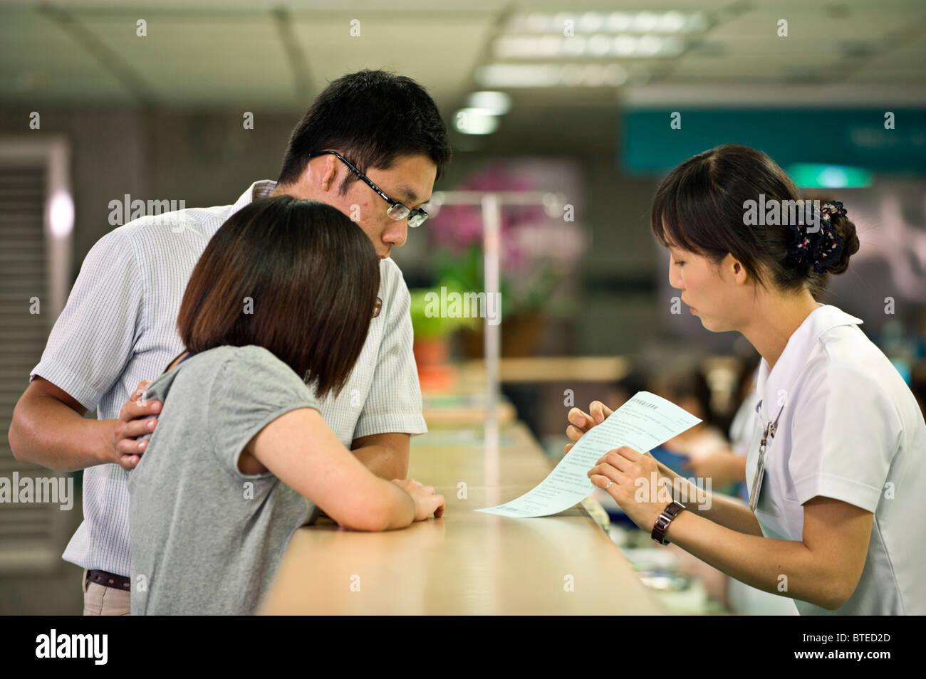 Nurse Explaining To Patient At Nursing Desk In Hospital, Taiwan