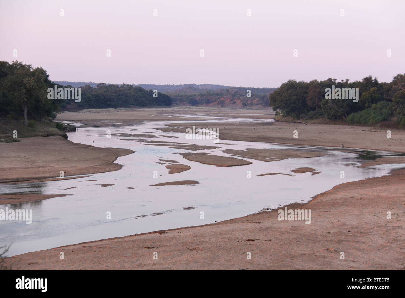 Mwenezi River bed winding with trees on either side of the banks - Stock Image
