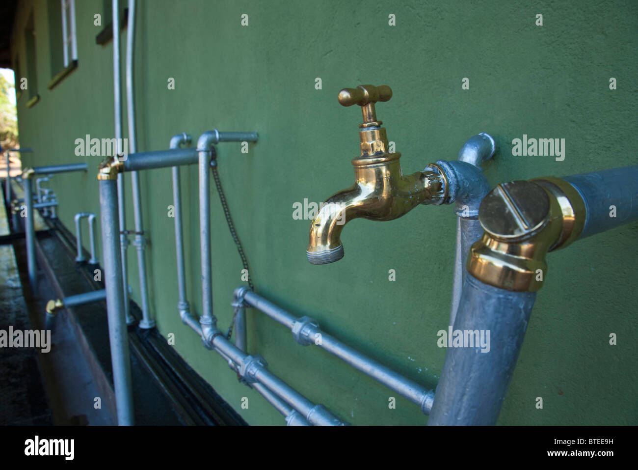 Shiny, clean taps and brass pipe fittings in Simuwini camp showing care and maintenance - Stock Image