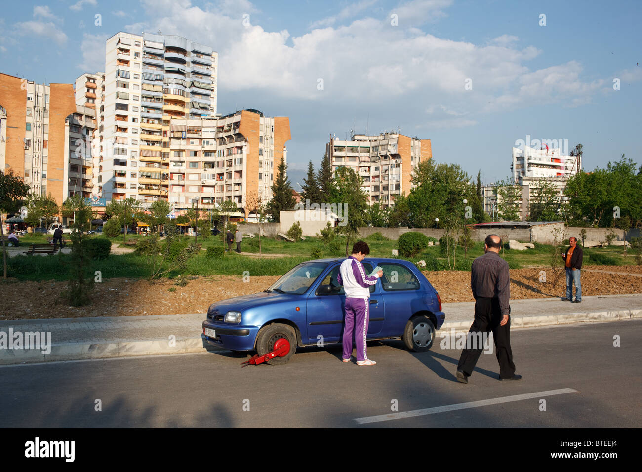 A woman with a traffic ticket and her car clamped with wheel clamp due to illegal parking in Tirana, the capital - Stock Image