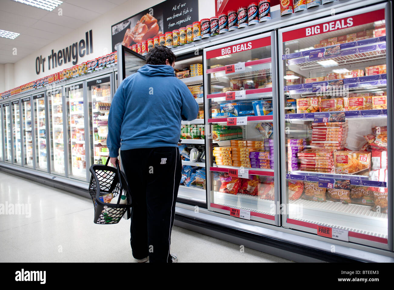 A man looking for an item in the frozen food section of Co-Op supermarket, UK - Stock Image