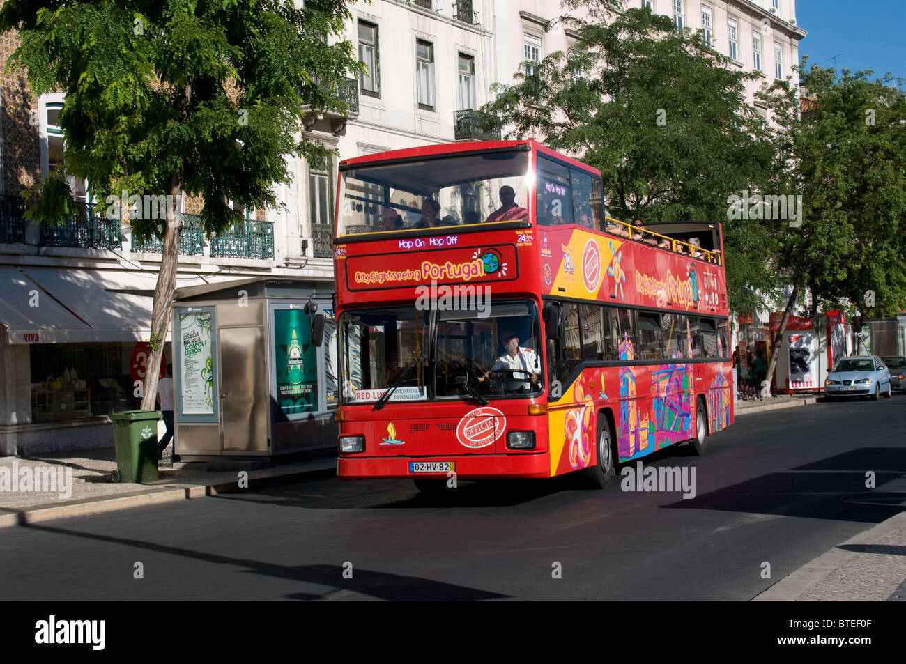 A Citysightseeing Portugal open top double deck bus carries tourist theough the Restaurdores area of Lisbon - Stock Image