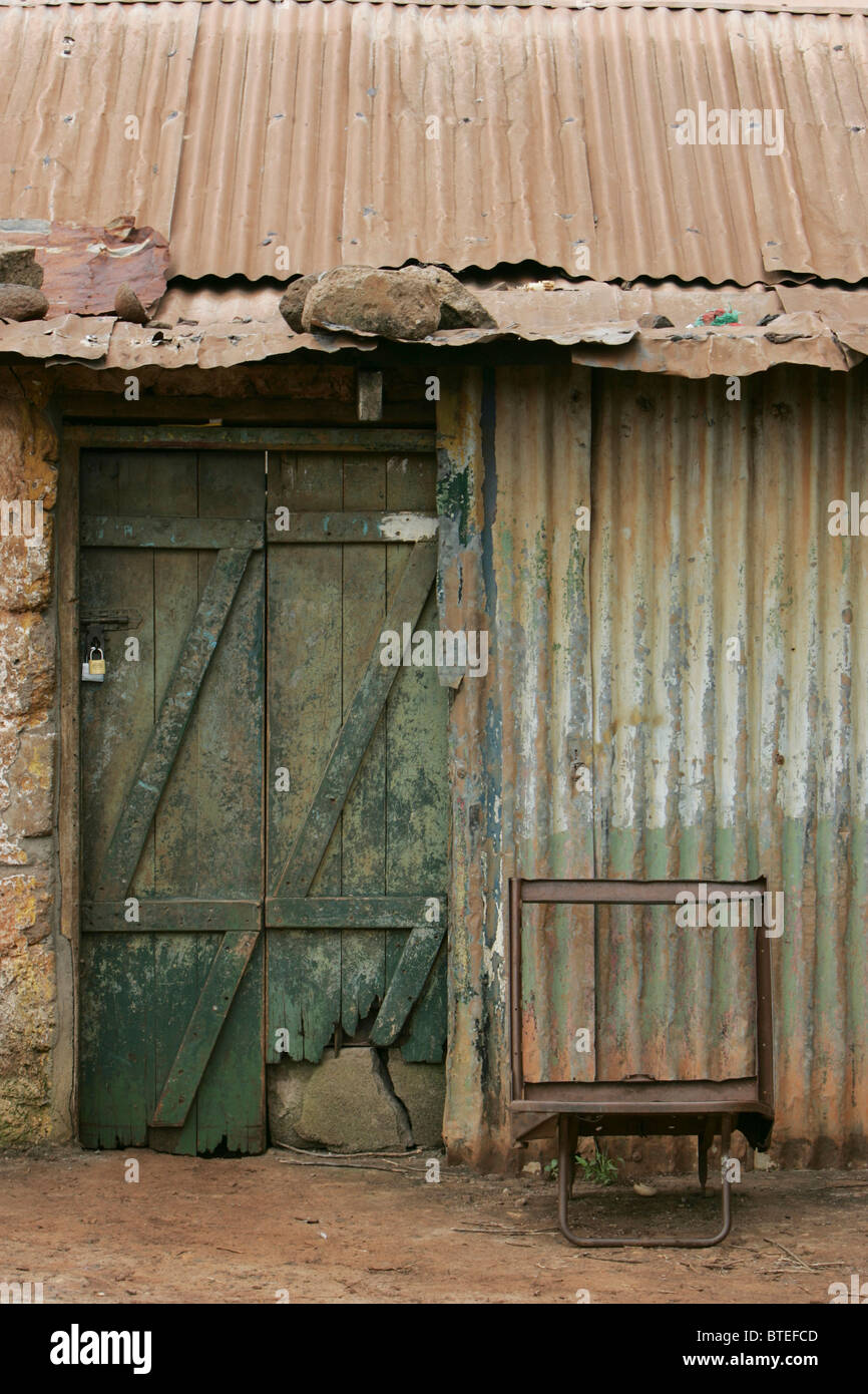 Old chair next to door of derelict corrugated iron and mud-brick house - Stock Image