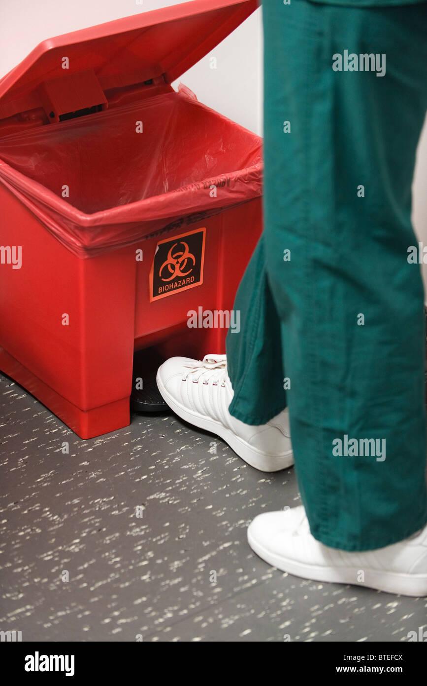 Throwing away medical waste in biohazard garbage can - Stock Image