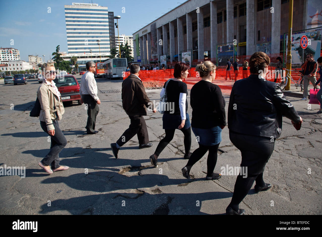 Young people go to work in the morning at the Skanderbeg Square in Tirana, the capital of Albania. - Stock Image