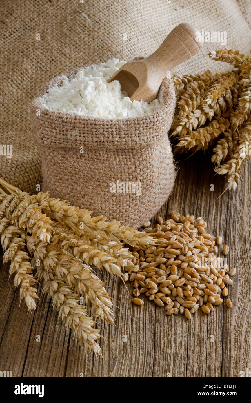 Wheat ears and flour in burlap bag - Stock Image