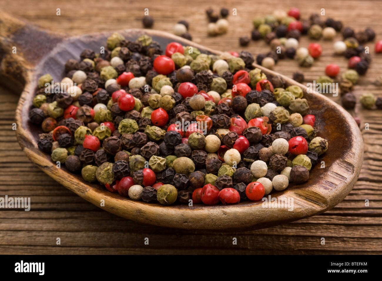 Color pepper and very old wooden spoon - Stock Image