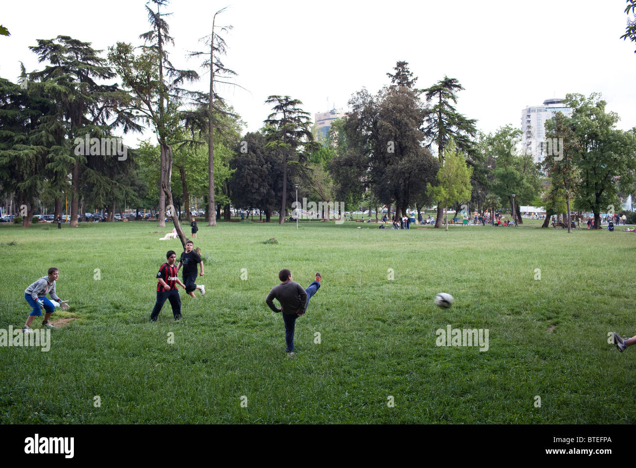 A group of boys play football in a park in Tirana, the capital of Albania. - Stock Image