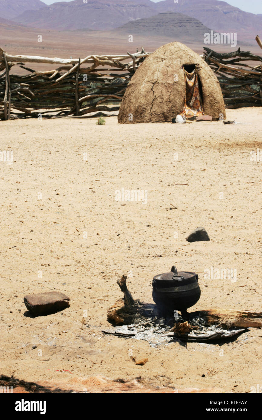 Three legged pot standing over ashes and a Himba hut in the background - Stock Image