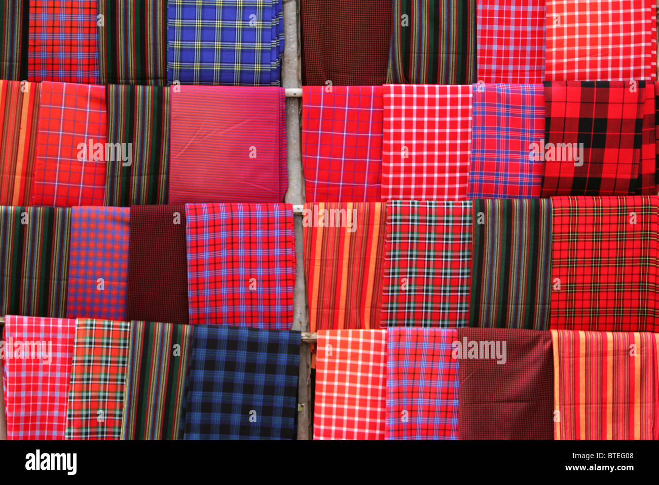 A display of brightly coloured shuka cloths - Stock Image