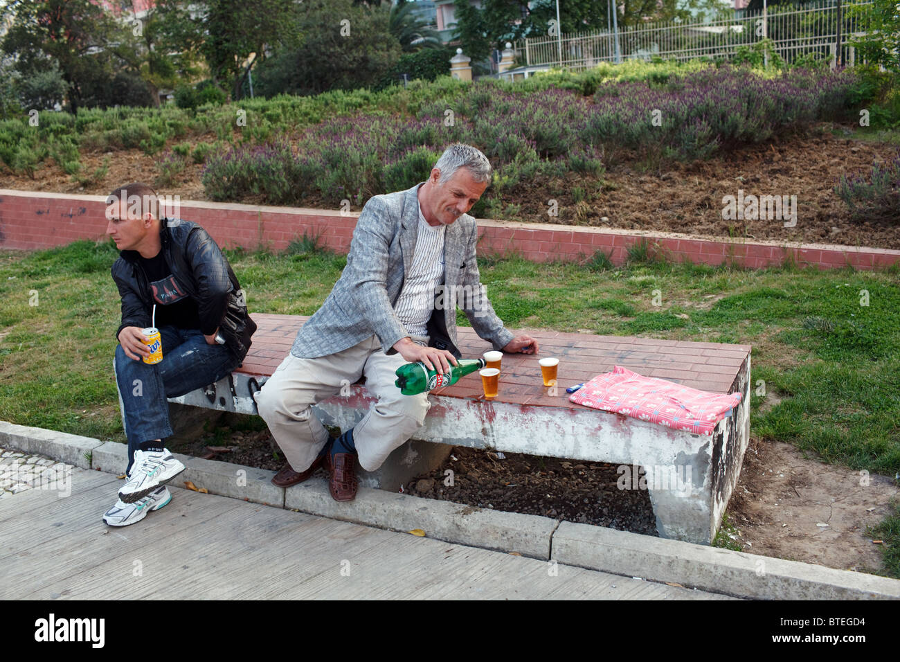 A man pours beer in a park in Tirana, the capital of Albania. - Stock Image