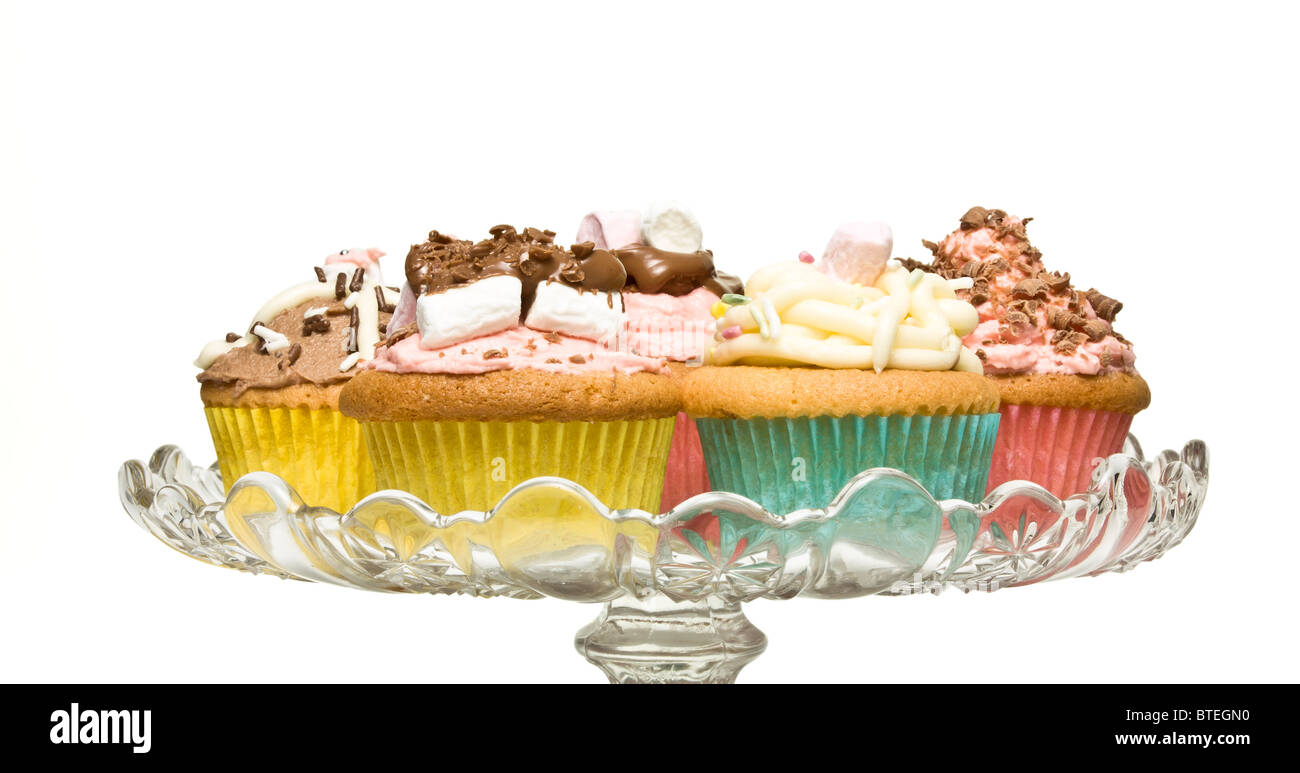 A selection of fancy homemade cupcake on glass pedestal cake stand. - Stock Image
