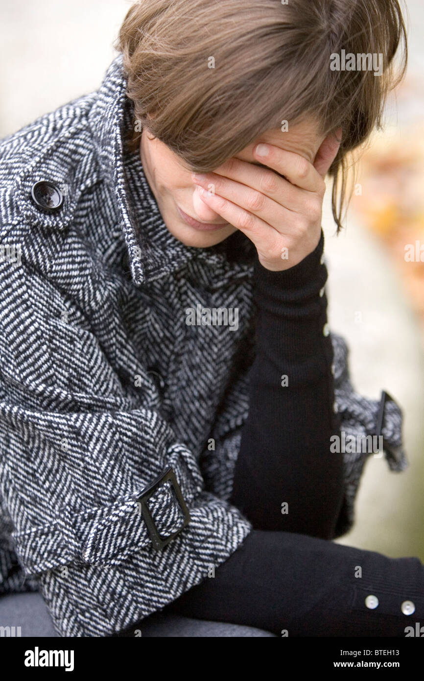 Woman covering her eyes - Stock Image