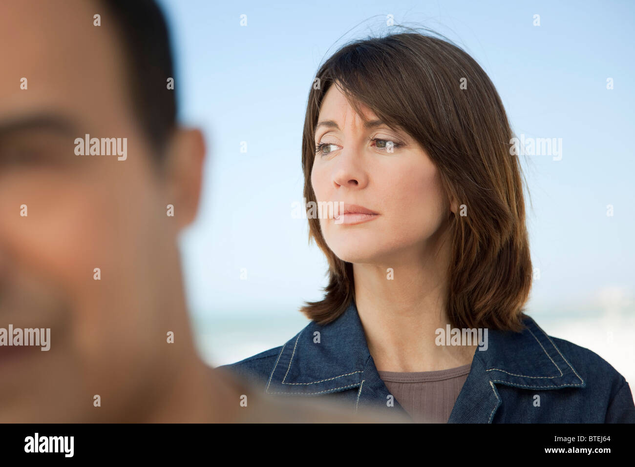 Woman looking away with furrowed brow, man in foreground Stock Photo