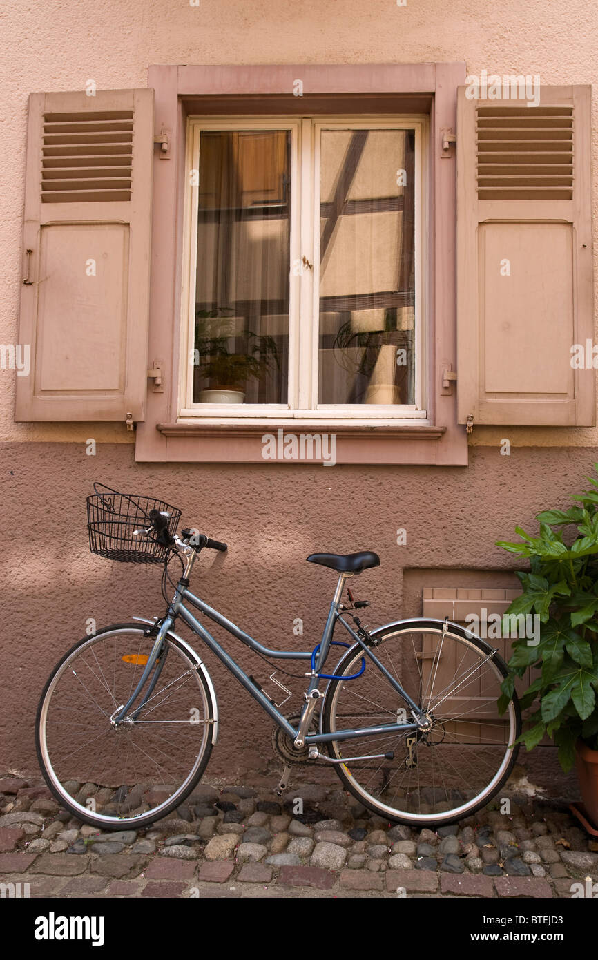 Bicycle parked under a window - Stock Image