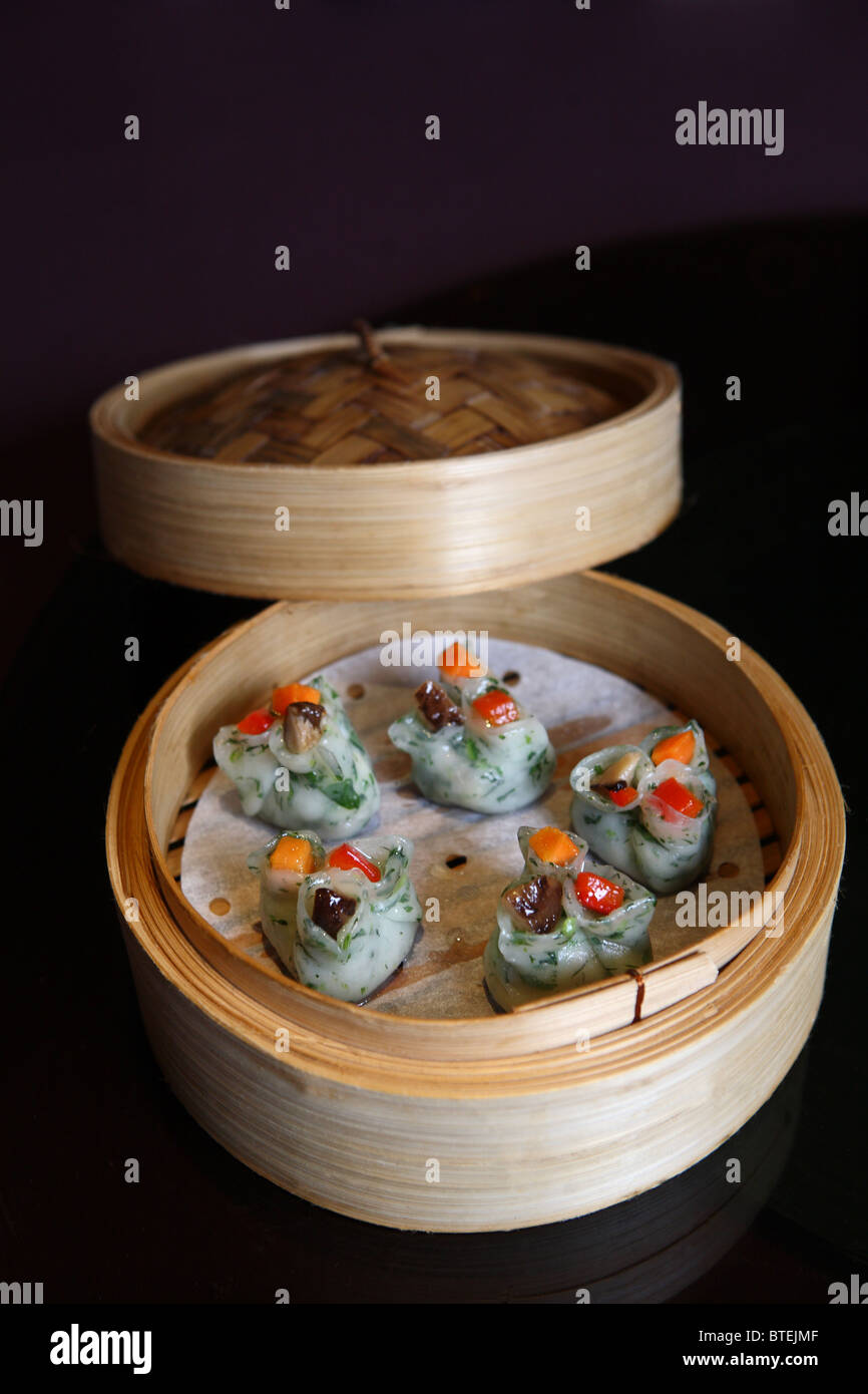 Chinese dumpling flour dim sum bamboo steam healthy Asian pork chicken vegetable colourful peppers - Stock Image