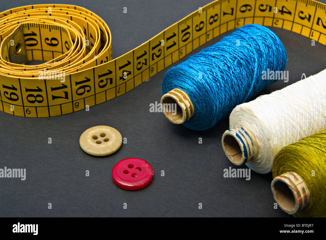Measure tape, a couple of thread bobbins and buttons - Stock Image
