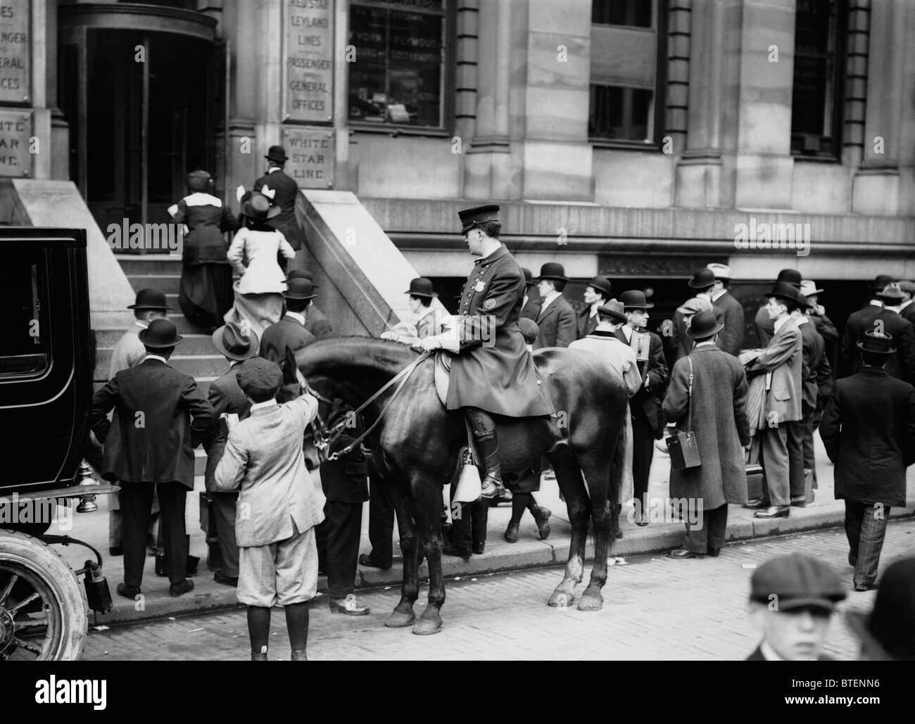 A policeman patrols outside the White Star Line offices in New York as crowds gather following the Titanic disaster - Stock Image