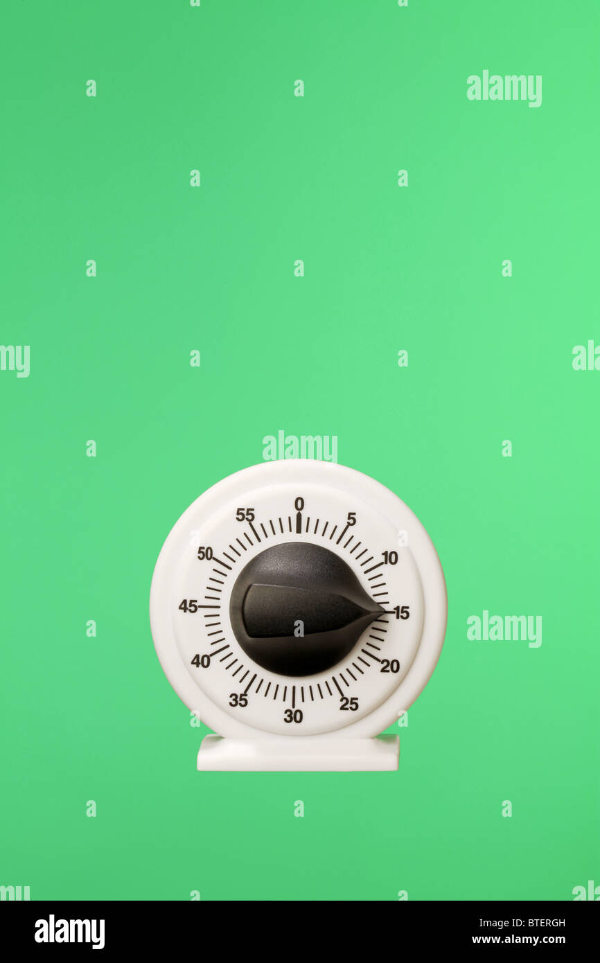 A count down timing device floating on a green background - Stock Image
