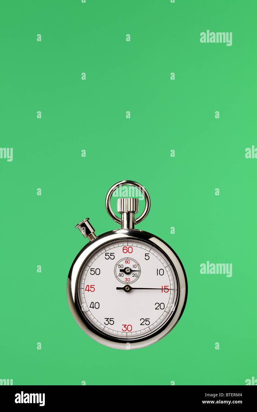 A stopwatch timing device floating on a green background - Stock Image