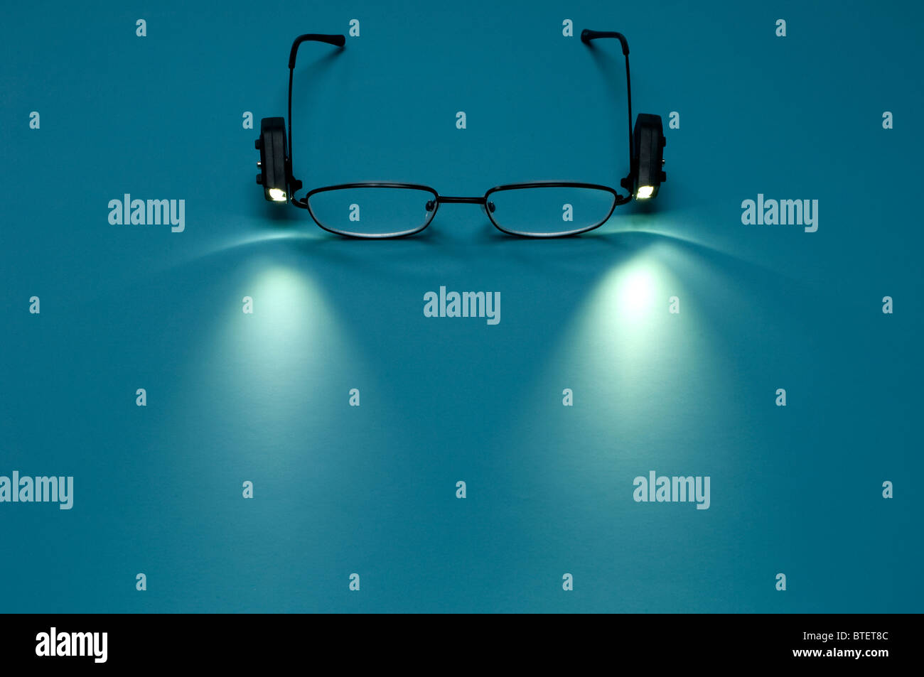 Reading eyeglasses with small lights attached to the frames. Light is projected on the surface. - Stock Image