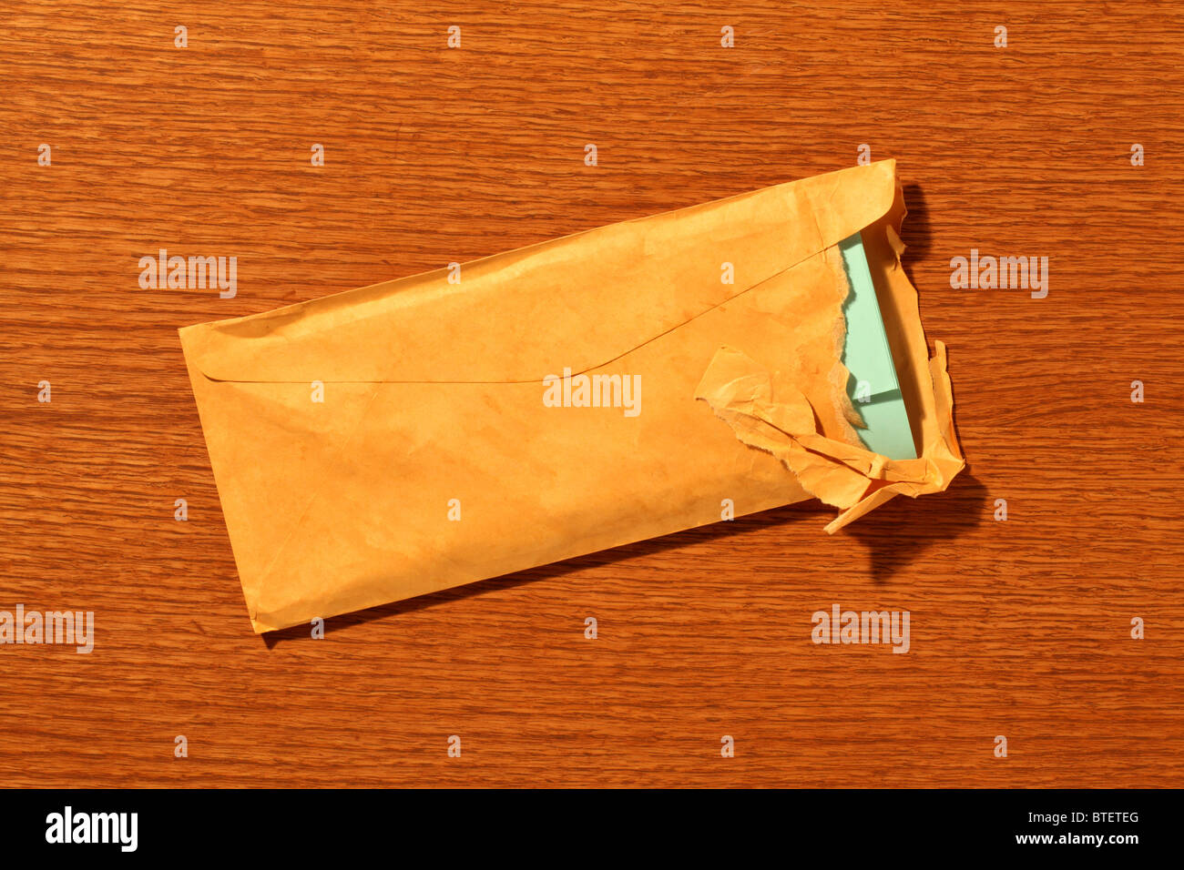 A used postal mailing envelope torn open. Brown wood grained background - Stock Image