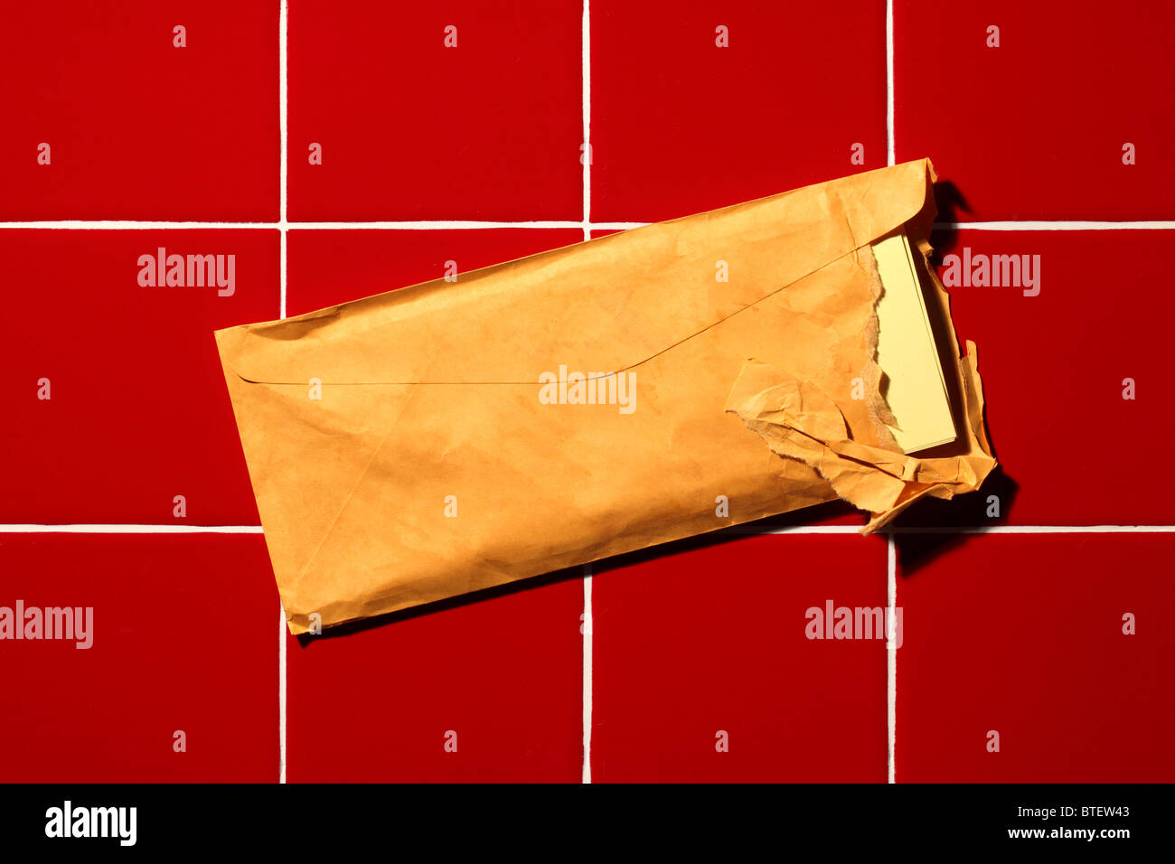 A used postal mailing envelope torn open. Red tiled background - Stock Image