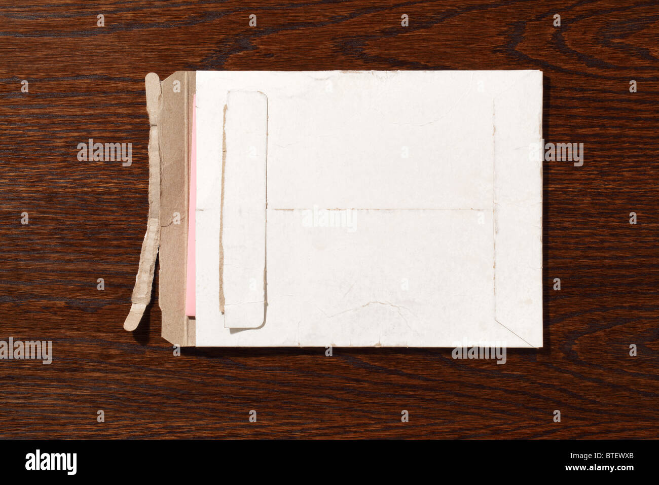 A used postal mailing envelope torn open. A dark brown wood desk background - Stock Image