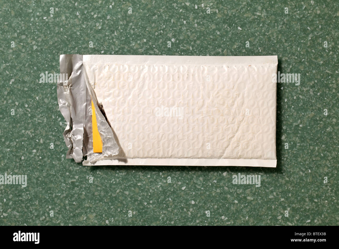 A used postal mailing envelope torn open. Green speckled counter top background - Stock Image