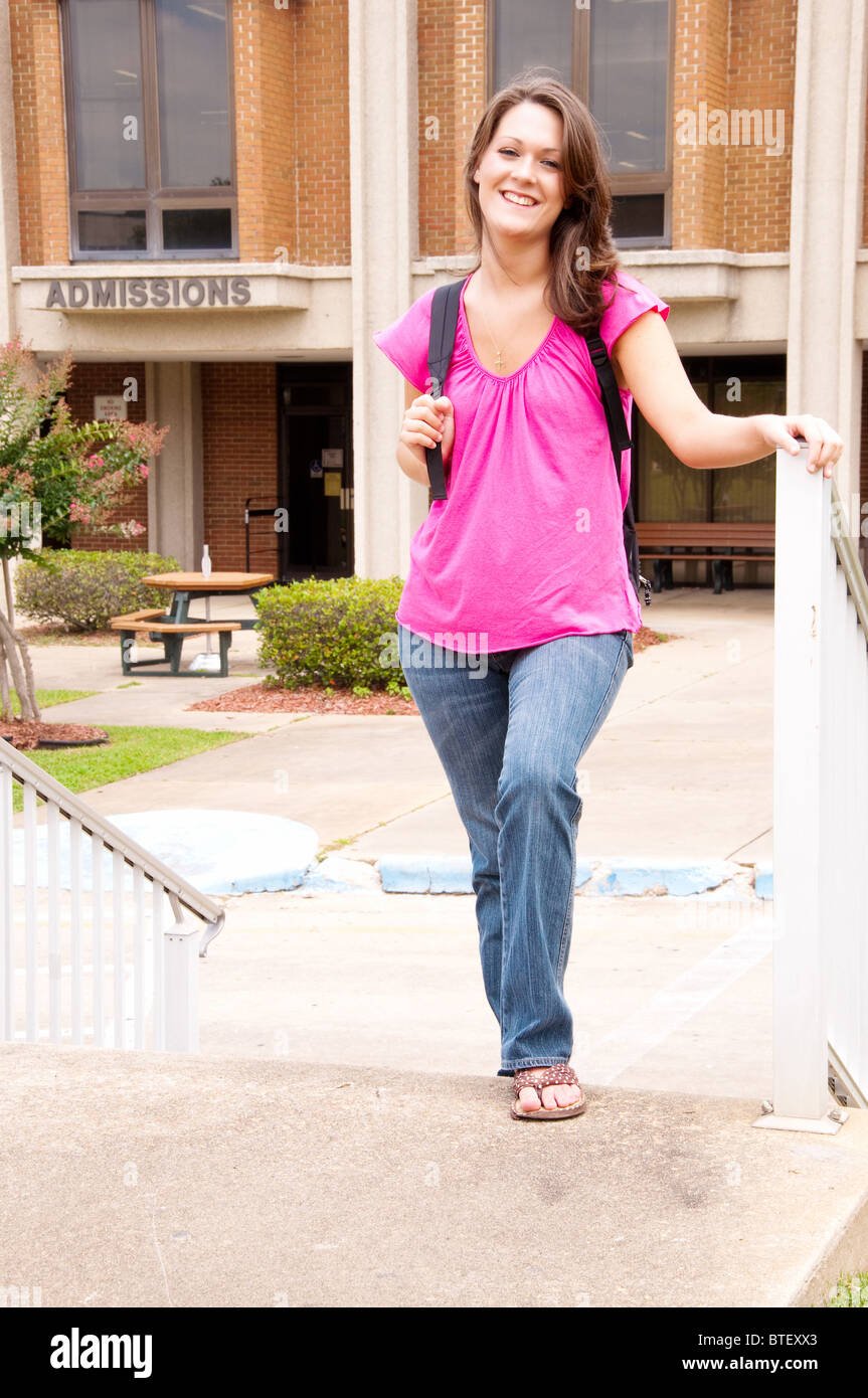 Female college student with backpack leaving admissions office at university. - Stock Image