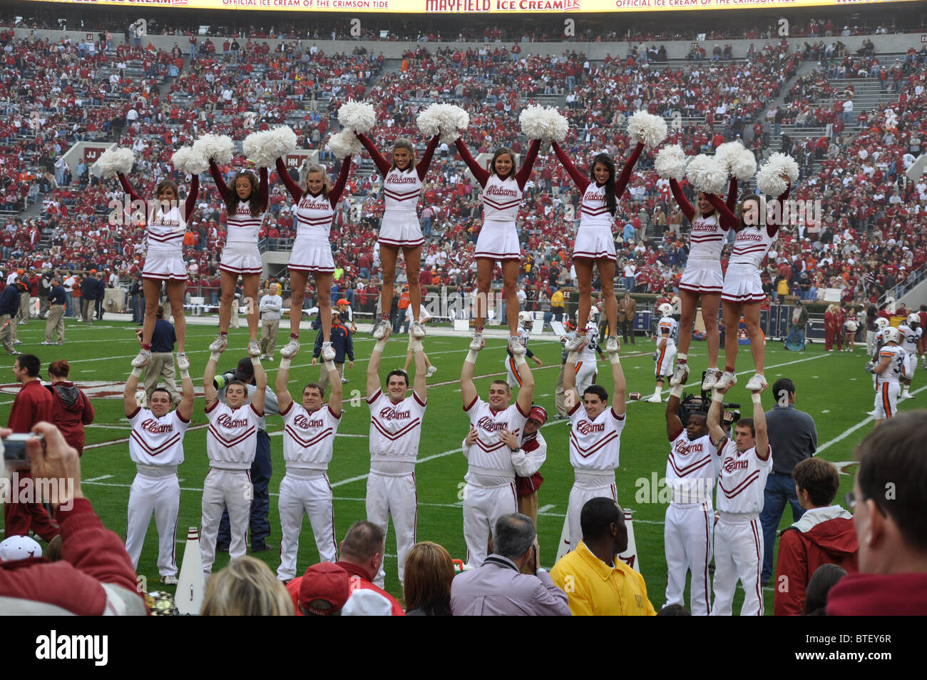 University of Alabama cheerleaders performing at football game. - Stock Image