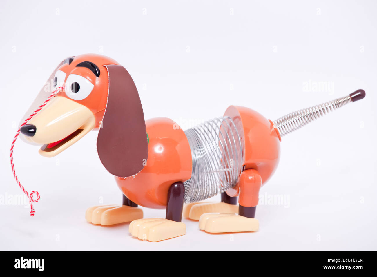 A close up photo of a childs toy Slinky dog character from the Toy Story films against a white background - Stock Image