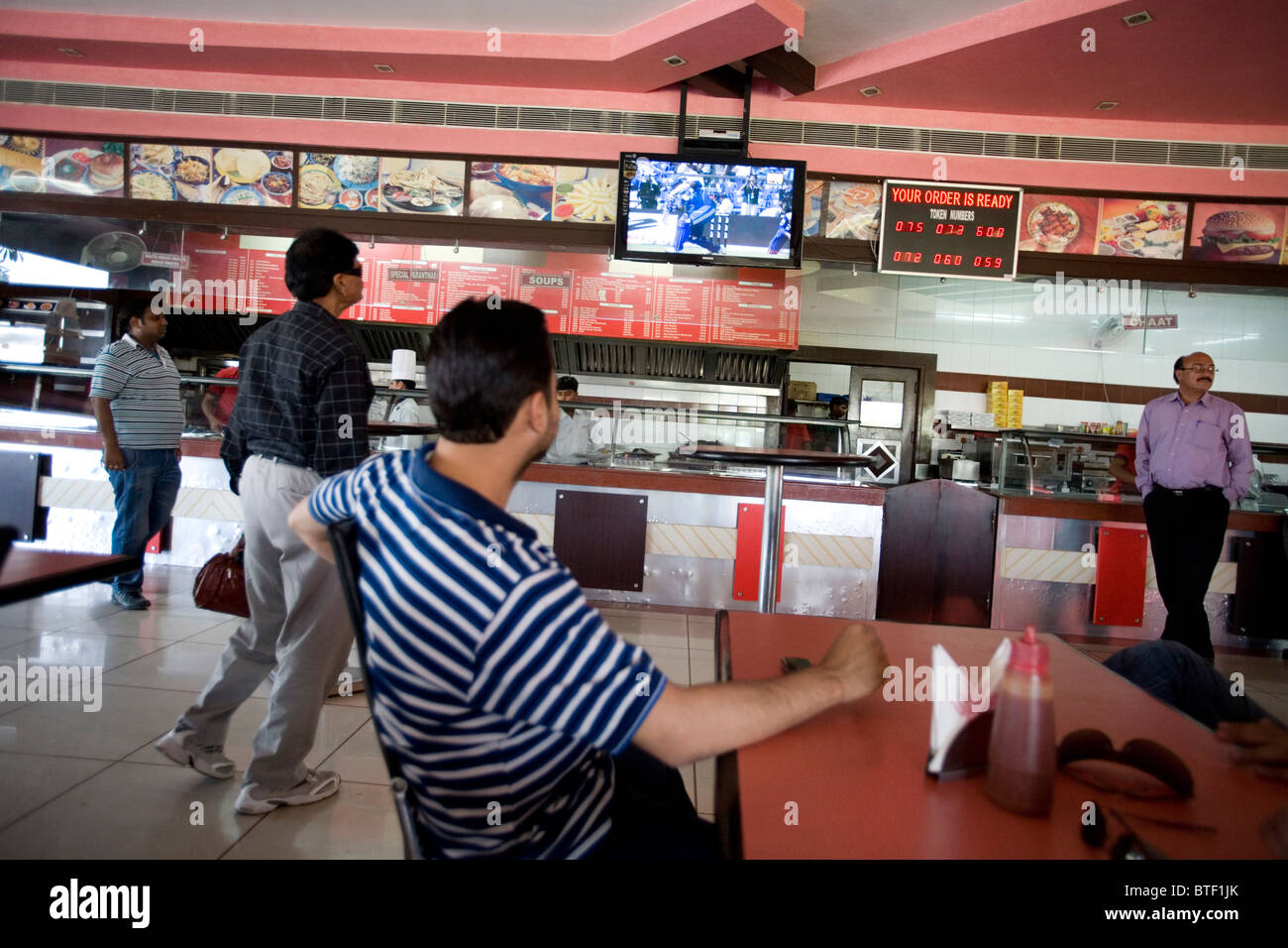 Fast-food shop in India showing cricket game on tv screen. - Stock Image