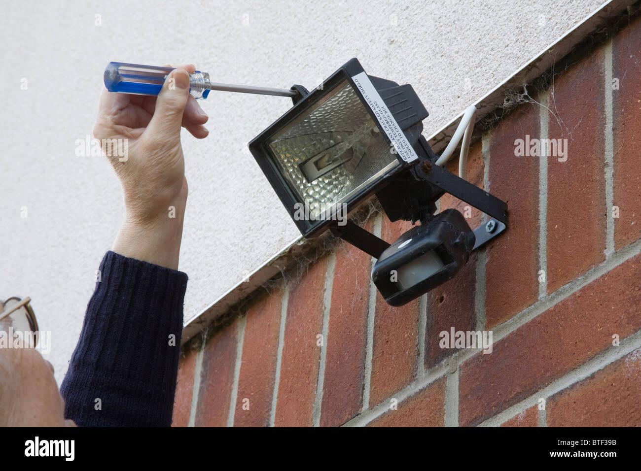 Close up woman using screwdriver to open external security light to close up woman using screwdriver to open external security light to change bulb aloadofball Gallery