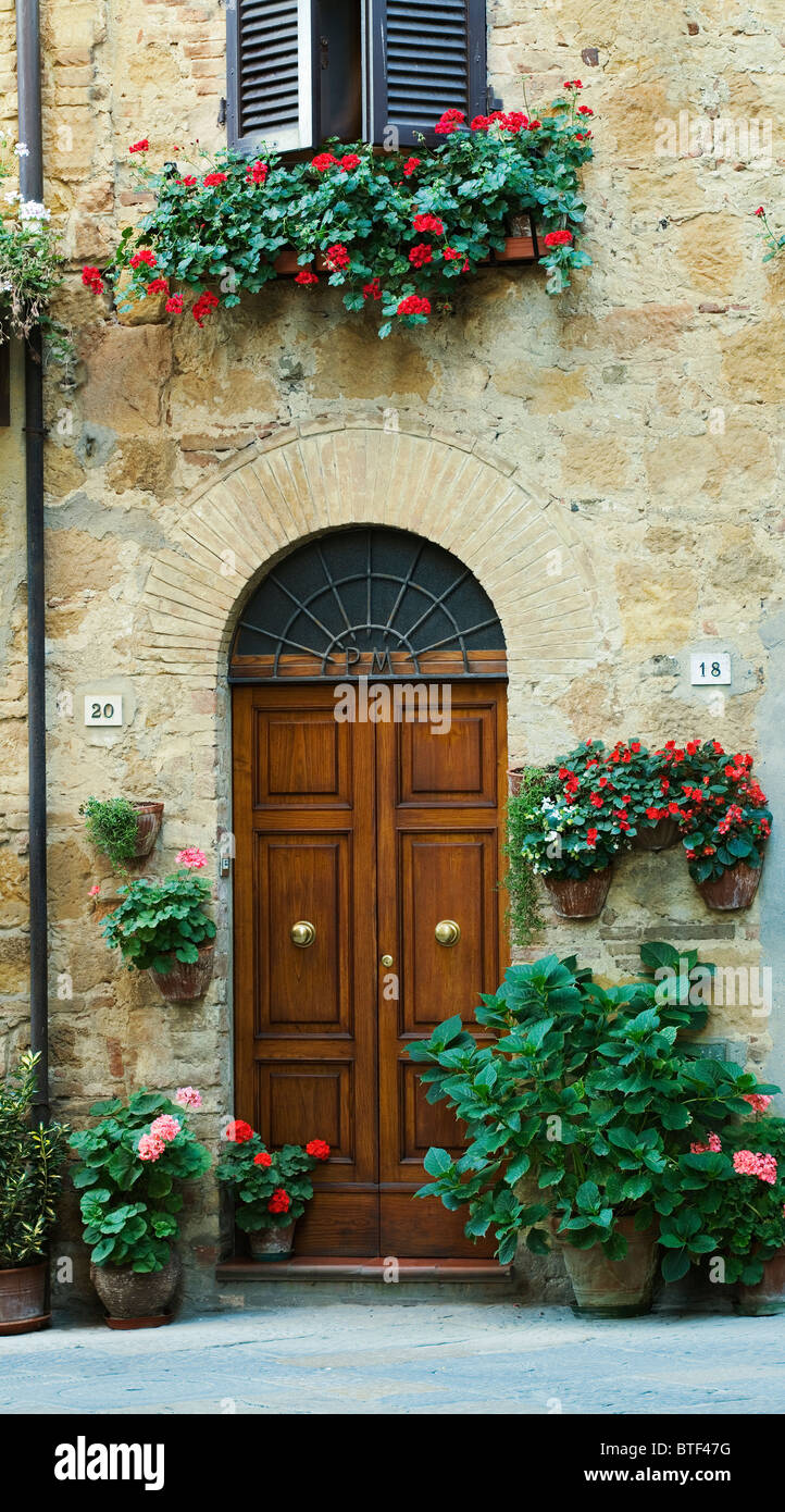 Pienza, doorway with pots of Granium flowers, Tuscany, Italy - Stock Image