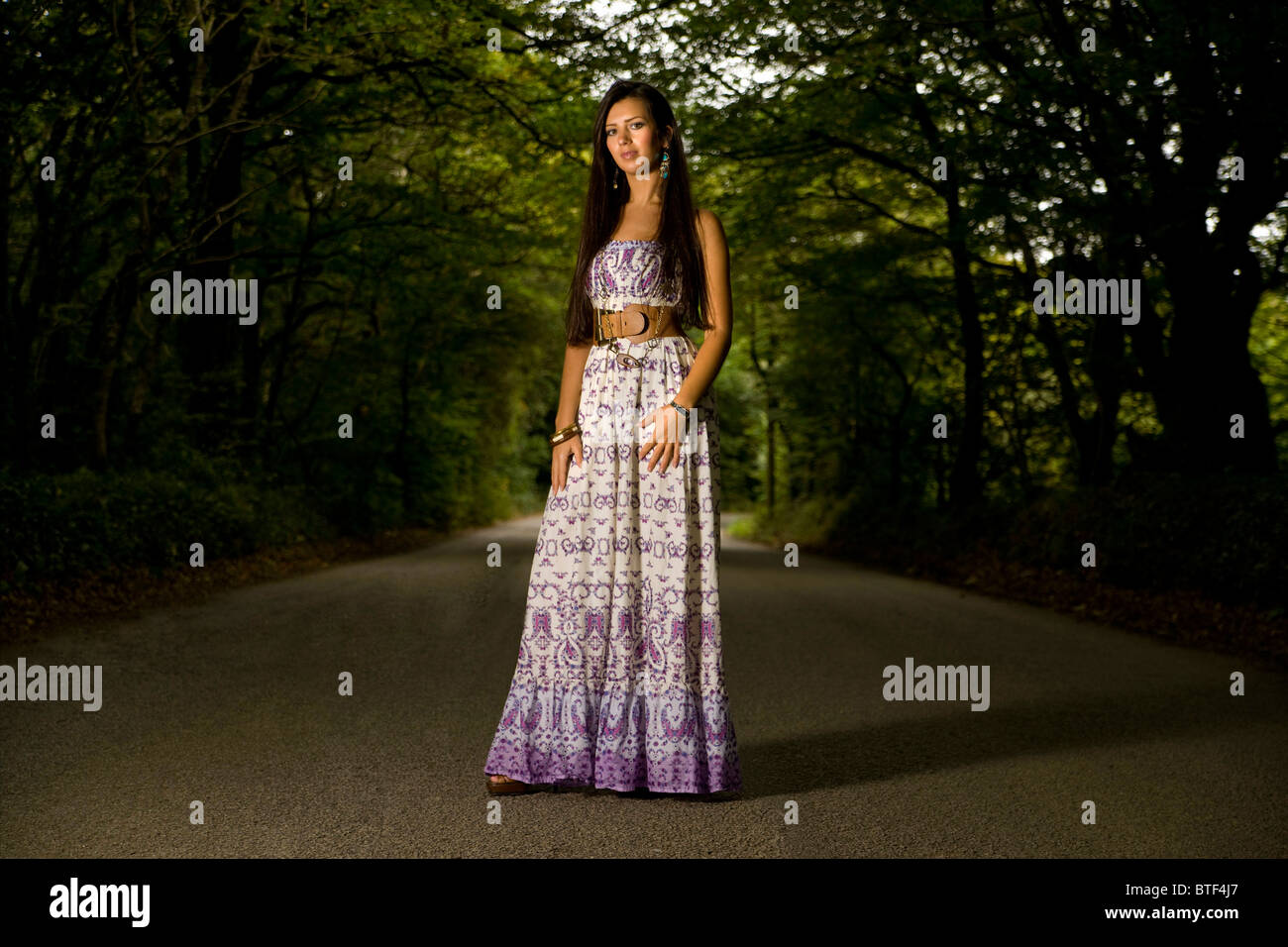 english pretty model woman standing in the middle of a tree lined road wearing a summer floral dress - Stock Image