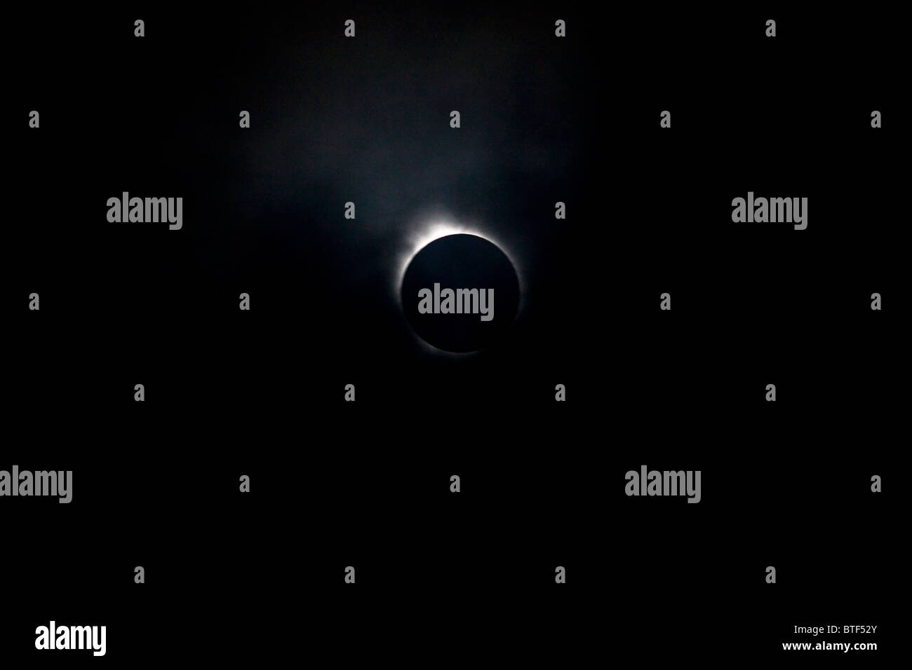 The 2010 total solar eclipse photographed at sea near Tahiti in the South Pacific ocean.  Clouds partly obscured - Stock Image