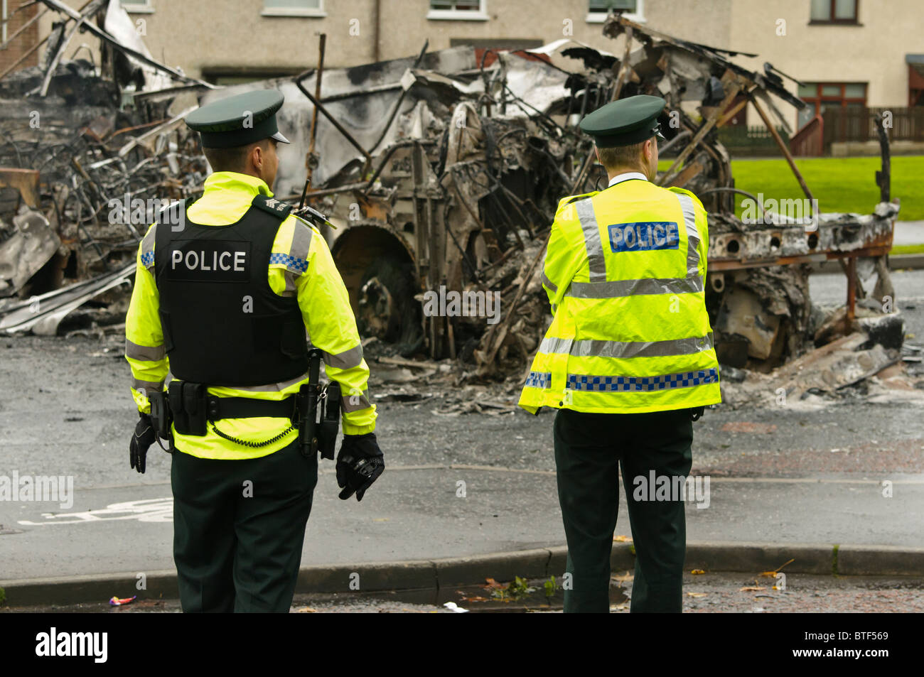 Two police officers at the scene of civil unrest, where a bus was hijacked and burned out. - Stock Image