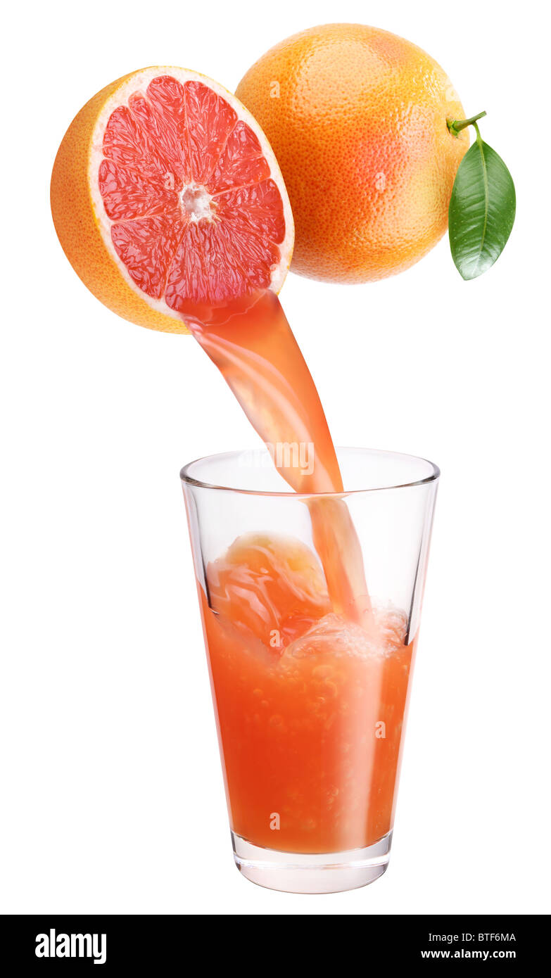 Fresh grapefruit juice flowing from cut grapefruit into the glass. - Stock Image