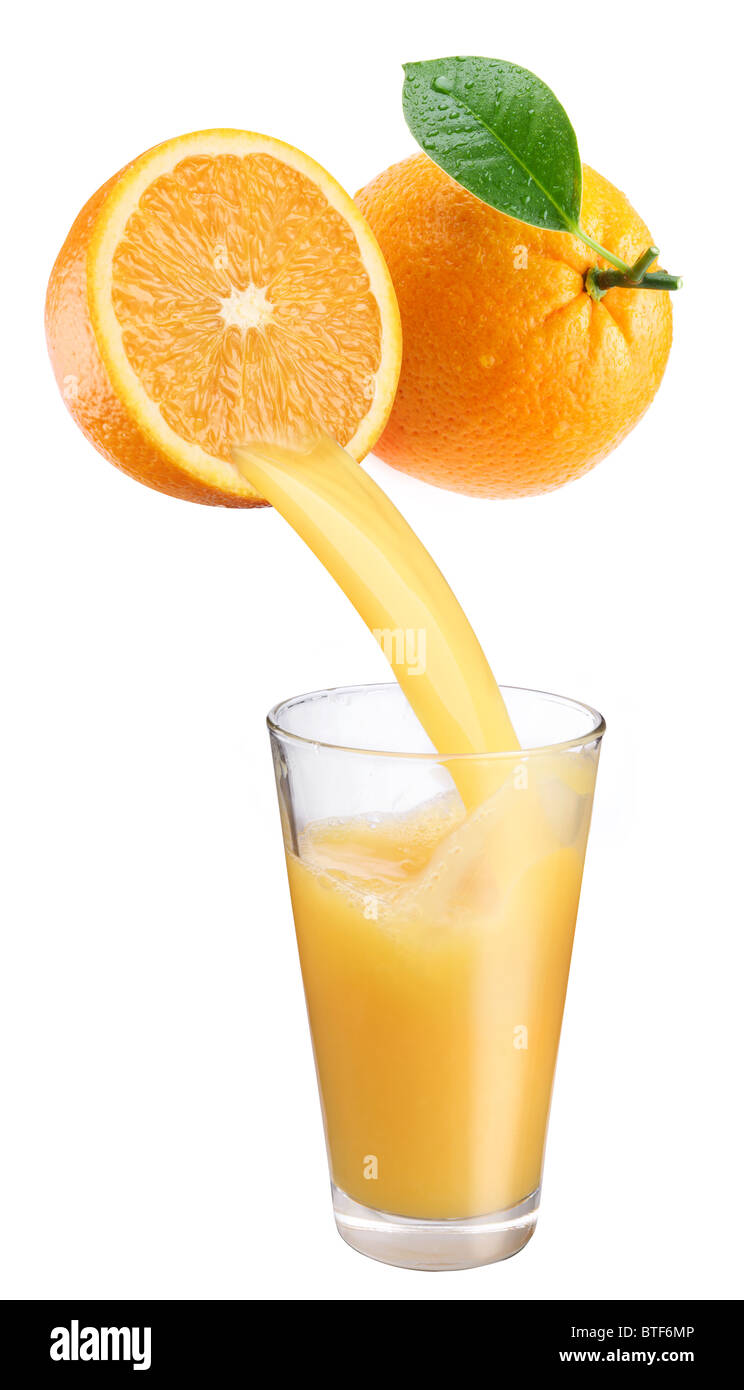 Fresh orange juice flowing from cut orange into the glass. Isolated on a white background. - Stock Image