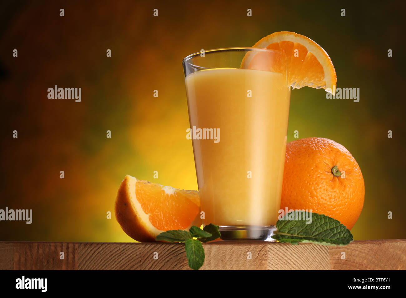 Still life: oranges and glass of juice on a wooden table. - Stock Image