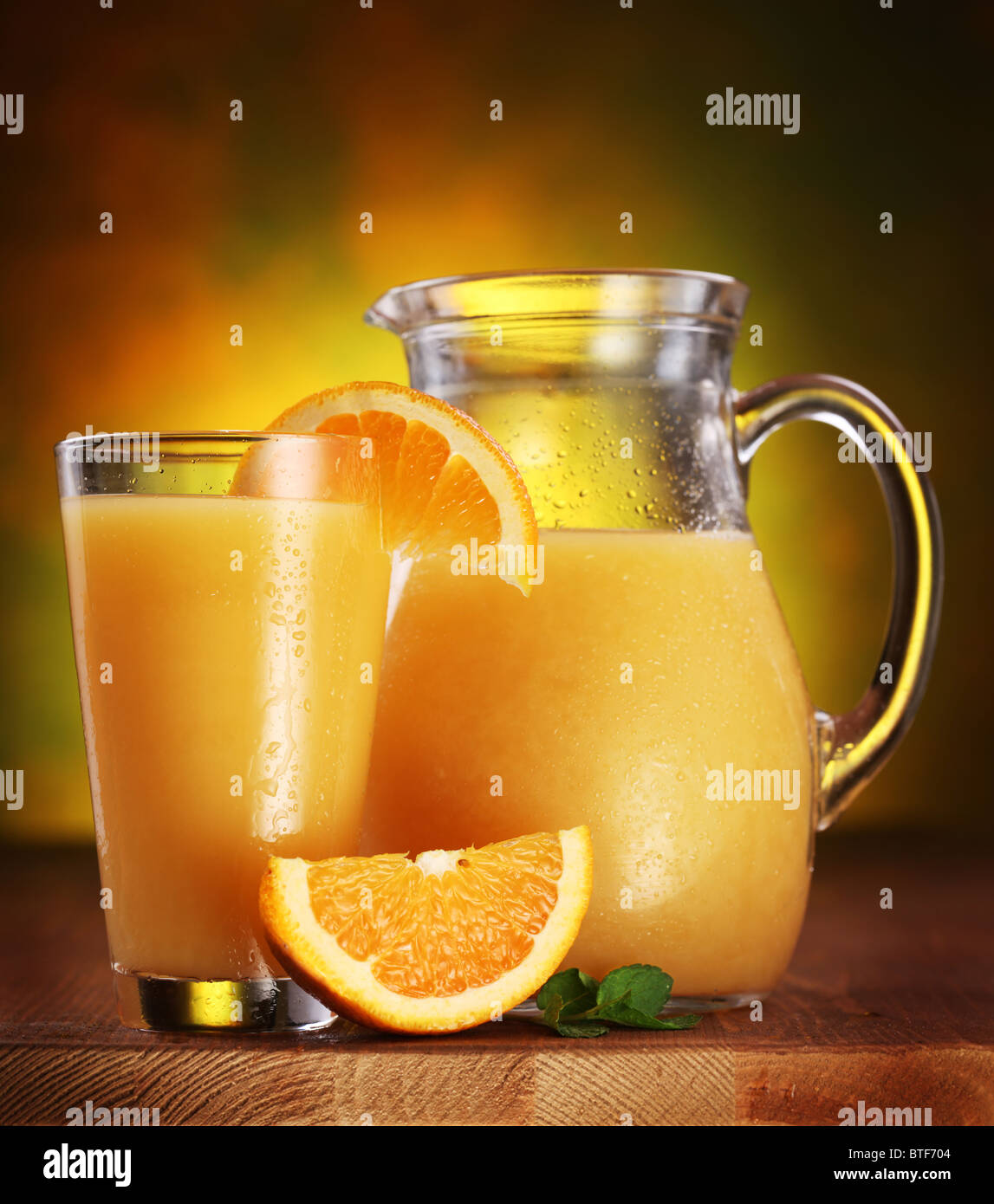 Still life: oranges, glass of juice and jug full of juice on a wooden table. - Stock Image
