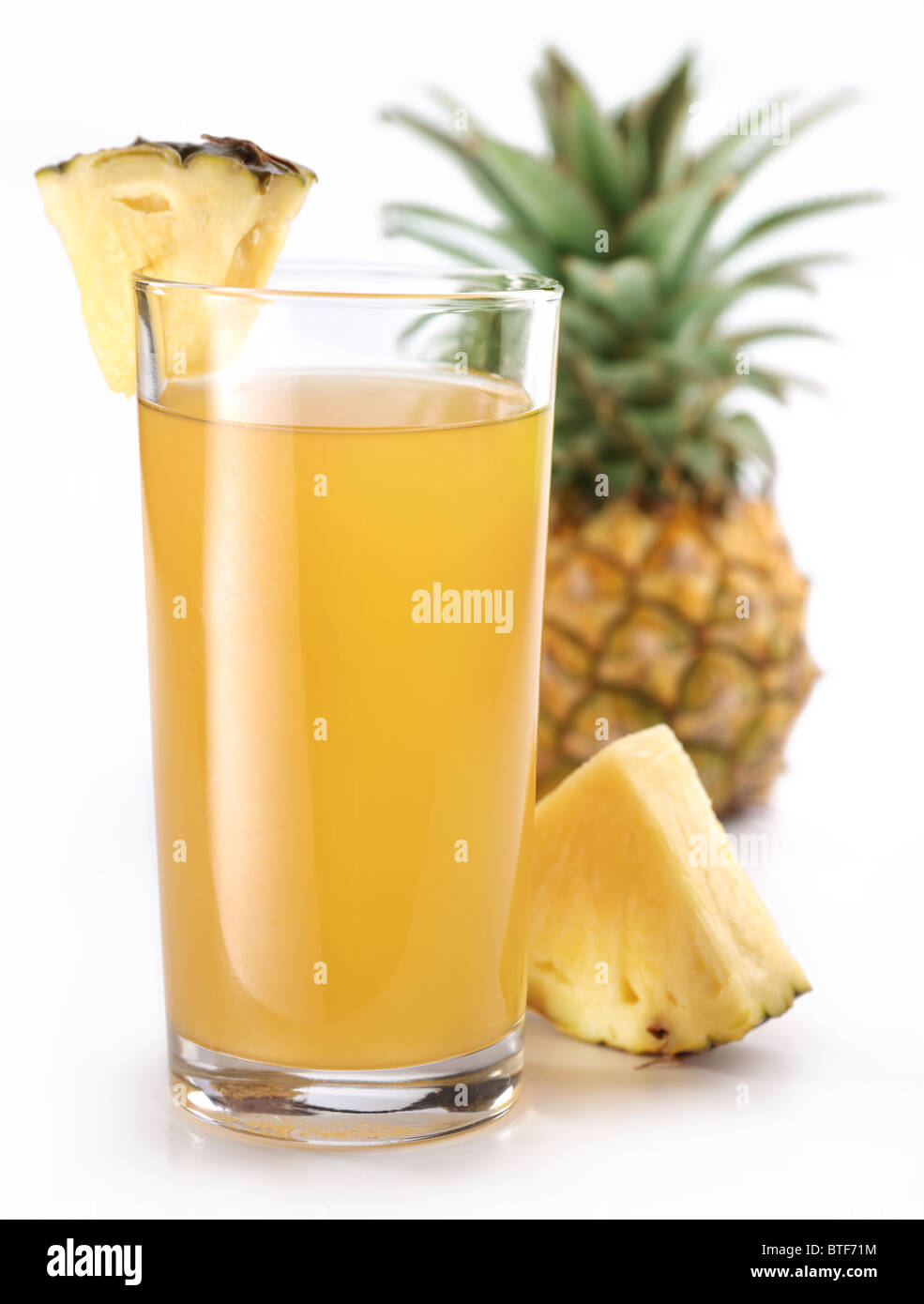 Full glass of fresh pineapple juice and pineapple fruit on the back. - Stock Image