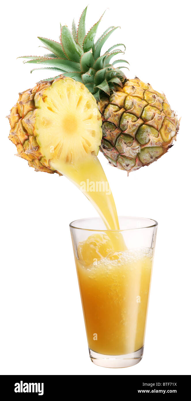 Fresh pineapple juice flowing fromcut pineapple into the glass. - Stock Image