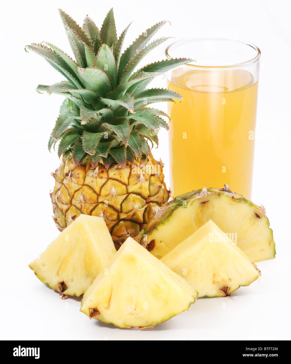 Full glass of fresh pineapple juice and pineapple fruit in the front. - Stock Image