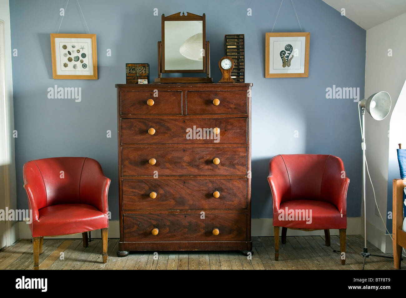 Old pine chest of drawers and leather chairs in bedroom of Victorian terraced house - Stock Image